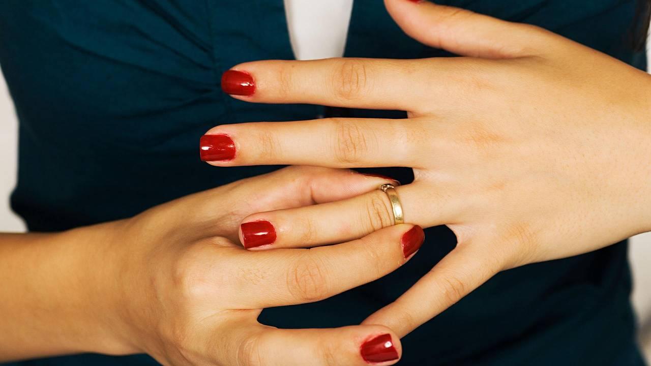 Женщина снимает кольцо с пальца.